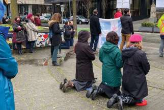 Catholics kneel to pray for churches to open outside Vancouver's Holy Rosary Cathedral.