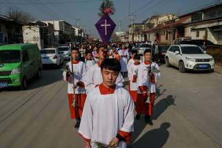 Altar servers lead a Palm Sunday procession March 25 in Youtong, in China's Hebei province.