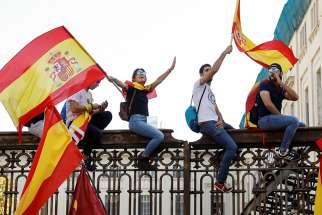 People wave Spanish flags during an Oct. 8 demonstration organized by the Catalan Civil Society organization in Barcelona, Spain.