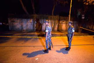 Bangladeshi security officials in Dhaka stand close to the spot where Tavella Cesare, an Italian aid worker, was killed Sept. 28, the previous day. Unknown assailants also shot an Italian priest in northern Bangladesh Nov. 18