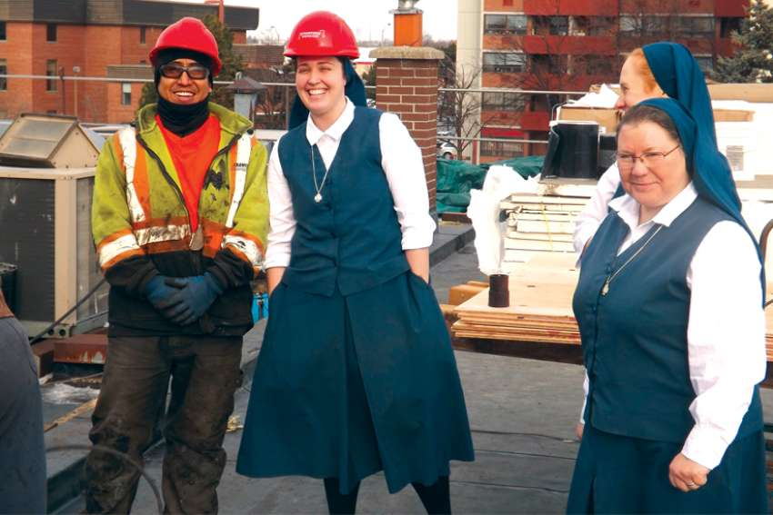 Sr. Carly Paula Arcella joins the hard-hatted crew on the roof of Pauline Books & Media Centre while local superior Sr. Catherine Bennett, right, and Sr. Amanda Marie Detry, background, look on.