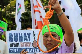 A woman holds up a noose during a Feb. 18 protest against plans to reimpose the death penalty, promote contraceptives and intensify the drug war at the Walk for Life in Manila.