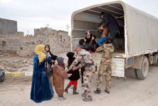 Iraqi soldiers evacuate families from Ramadi, Iraq, Feb. 3, after the city was recently recaptured by Iraqi forces. A European bishops' commission has welcomed a move by the European Parliament to classify atrocities and religious cleansing by the Islamic State as genocide.