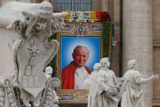 A banner depicting St. John Paul II hangs from the facade of St. Peter's Basilica at the Vatican April 27.