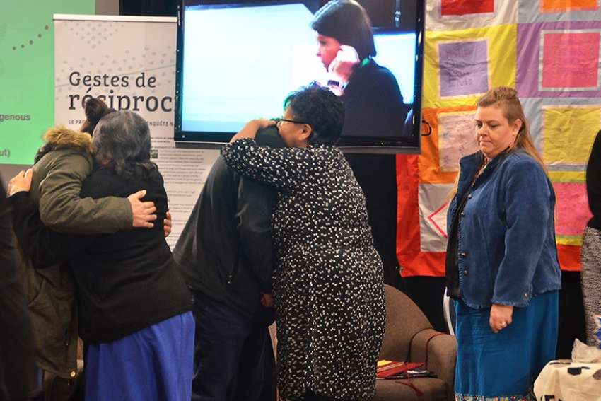 People console one another during the National Inquiry Into Missing and Murdered Indigenous Women and Girls public hearings in Edmonton, Alberta, Nov. 7