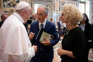 Pope Francis greets attendees during a meeting with doctors, patients and members of the Italian Association of Medical Oncology at the Vatican.