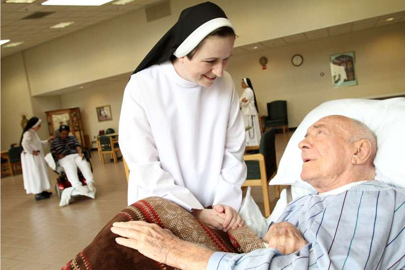 A palliative care patient chats with a sister in New York in this 2011 file photo. The Catholic Health Alliance of Canada is promoting palliative care as an option to assisted suicide, which is legal now after the Supreme Court struck down the ban.