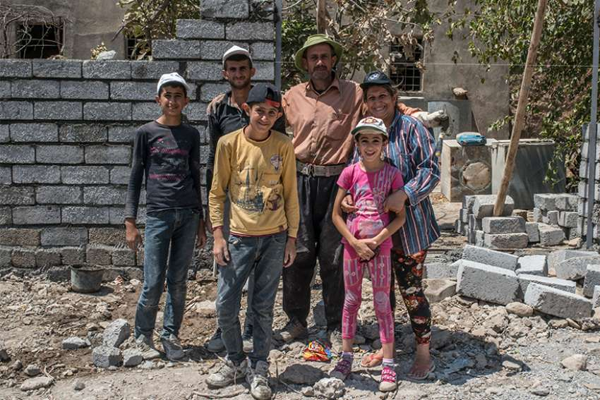 A Catholic family working to repair their family home damaged by Islamic State militants poses in 2017 in the Christian town of Karamdes, Iraq.