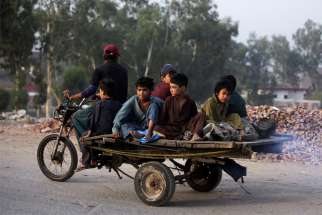 Boys from an Afghan refugee family ride on a motorcycle cart as they head to search for recyclables in Lahore, Pakistan, June 20, 2019. The Vatican said Pope Francis will celebrate Mass in St. Peter's Basilica July 8 with migrants, refugees and volunteer rescue teams.