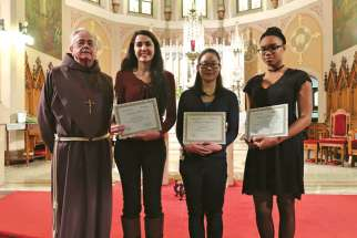 Franciscan Fr. Damian MacPherson, left, stands with the winners of the 14th annual Friar's Student Writing Award. From left to right, Sabrina Quartarone (third place), Jessica Nguyen (first place) and Ruthann Lemonius (second place).