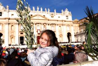 A girl holds palms before the start of Palm Sunday Mass celebrated by Pope Francis in St. Peter's Square at the Vatican March 29.
