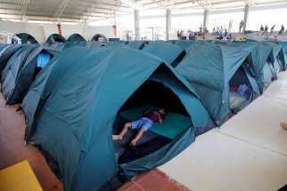 A child sleeps in a tent April 4, 2017, at a shelter for people left homeless after mudslides in Mocoa, Colombia. Caritas Colombia is working with international and national agencies to assess needs and generate a plan for the thousands of families left homeless.