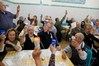 People raise their ice cream cones donated by Pope Francis as they toast the pope at a Sant'Egidio soup kitchen in Rome April 23. In honor of his name day, the feast of St. George, the pope donated 3,000 servings of ice cream to soup kitchens and homeless shelters around Rome.