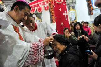Chinese Catholic priests baptize new believers during a 2013 Easter Vigil in a church in Shenyang, China. A papal visit to China does not appear likely anytime soon, according to experts on the church in China.