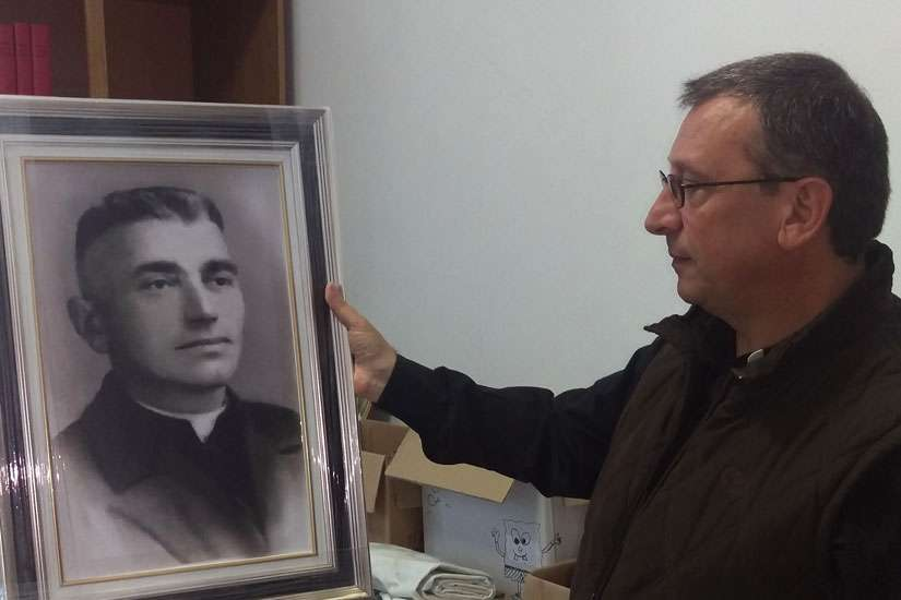 Franciscan Brother Vincenzo Foca holds a photo of Father Luigj Prendushi May 7 in Shkoder, Albania. Father Prendushi was killed in Albania under that country's former atheist regime and Brother Vincenzo has spent the last 24 years locating bodies of Catholics in Albania, some of whom, like Father Prendushi, are on Pope Francis' list of martyrs.