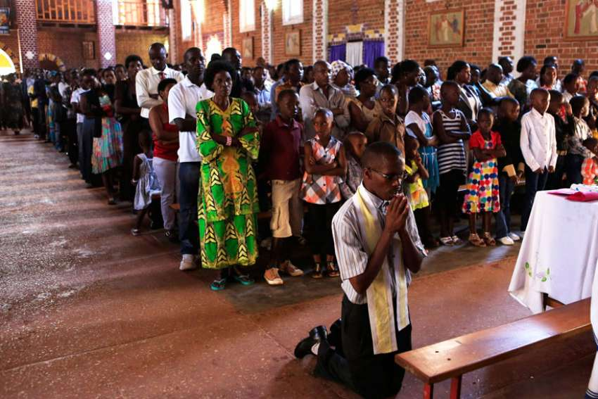 A man kneels in prayer during Mass at St. Famille Church in Kigali April 6, one day ahead of the commemoration of the 20th anniversary of the Rwandan genocide. An estimated 1 million people were murdered in acts of ethnic violence.