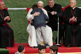 Pope Francis embraces Emanuele, a boy whose father died, as he visits St. Paul of the Cross Parish in Rome April 15.