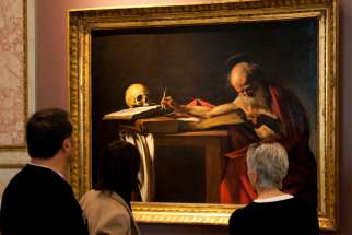 "Visitors are pictured in a file photo looking at a Caravaggio painting titled ""St. Jerome Writing"" during an exhibition at the Galleria Borghese in Rome. Pope Francis released ""Scripturae Sacrae affectus"" (""Devotion to Sacred Scripture""), a new apostolic letter on the Bible, Sept. 30, 2020, coinciding with the 1,600th anniversary of St. Jerome's death."
