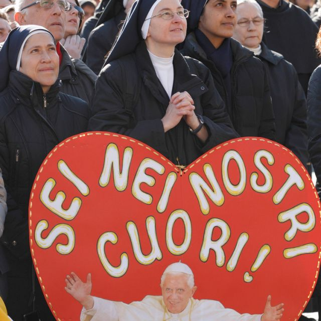 "Sister Benedetta Favreau holds a sign saying in Italian ""You are in our hearts,"" as she attends Pope Benedict XVI's recitation of the Angelus from the window of his apartment overlooking St. Peter's Square at the Vatican Jan. 15."