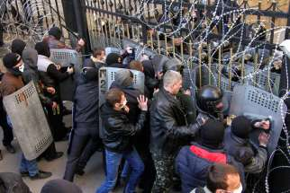 "Pro-Russia protesters scuffle with the police at the regional government building in Donetsk, Ukraine, April 6. A Ukrainian Catholic bishop has warned his church could lose its legal status under Russian rule, and pledged to use ""all possible means in th e international arena"" to defend it."