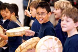 Students learning to play traditional drums at Brebeuf College School.