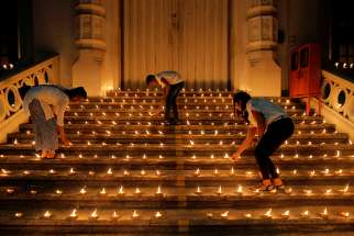 Young people light candles near the closed door of a church in Colombo, Sri Lanka, April 28, 2019, during a vigil in memory of the victims of a string of suicide bomb attacks across the island on Easter .