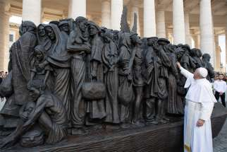 Pope Francis studies the bronze statue depicting migrants and refugees titled Angels Unawares by Canadian artist Timothy Schmalz.