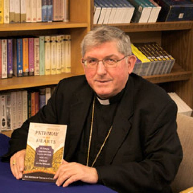 Toronto Archbishop Thomas Collins poses with a copy of his new book, Pathway to our Hearts.