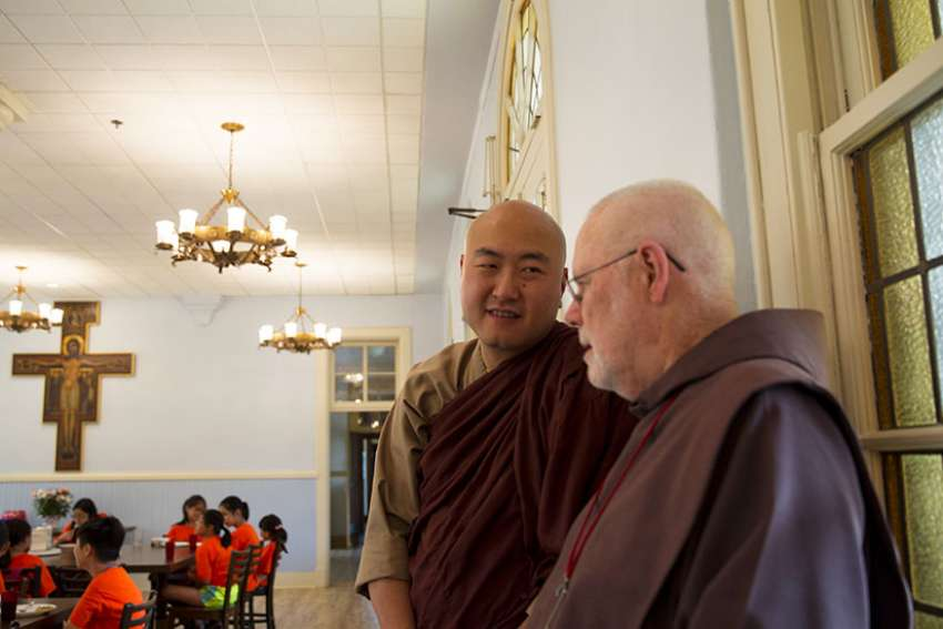 Venerable Sagarananda Tien and Father James Gardiner, a Franciscan Friar of the Atonement, talk as children from the U.S. Zen Institute summer camp eat lunch July 12 at the Franciscan Monastery of the Holy Land in Washington. The Buddhist children spent the afternoon learning about Christianity, St. Francis and the Franciscans as way to understand other traditions and cultures, said Tien.
