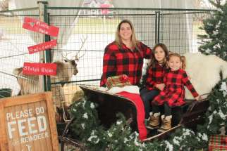 Sofia and Gabrielle Pagliaroli, with mother Adele and live reindeer, at Toronto's St. Simon School. Despite COVID-19, Ontario Catholic schools have kept up the Christmas spirit.