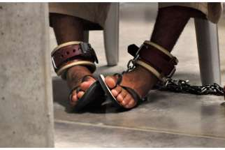 "In this photo, reviewed by a U.S. Department of Defense official, a detainee's feet are shackled to the floor as he attends a ""Life Skills"" class inside Camp 6 detention center at the Guantanamo Bay Naval Base in Cuba April 27, 2010."