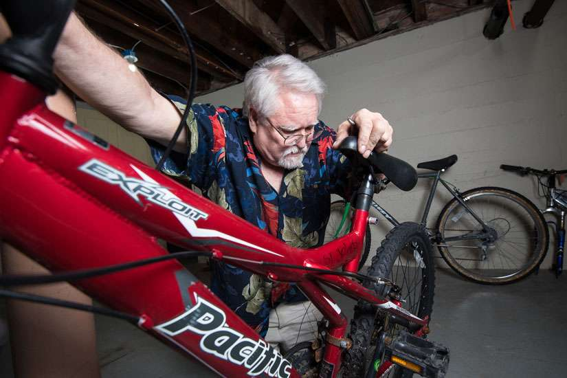 Tom Mayhew tests the brakes on a bicycle in the basement of St. John the Evangelist Church rectory in Green Bay, Wis. Mayhew, a retired dentist, was homeless and turned to the shelter after his practice went bankrupt. Now back on his feet, he says repairing bikes is a way for him to give back to the shelter.