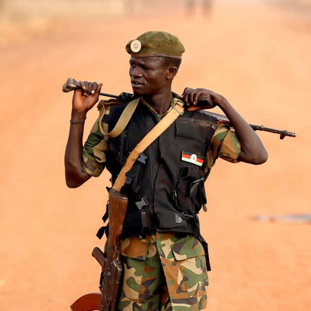 A South Sudan soldier walks on the front line in Panakuach April 24. Recent aerial bombardments, ground-force skirmishes and especially the increasingly hostile rhetoric of the leaders of Sudan and South Sudan have religious leaders worried about the pos sibility of all-out war.
