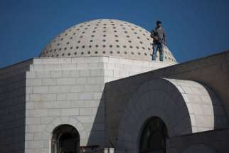 Police stand guard on the roof of a Jerusalem synagogue involved in a fatal attack Nov. 18. Two Palestinians are said to have killed four people with a meat cleaver and a knife before being shot dead by police, the deadliest such incident in six years in the holy city amid a surge in religious conflict.