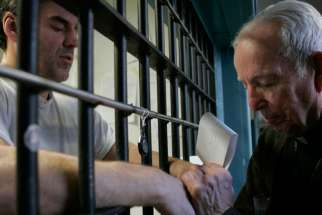 A priest prays with death-row inmate in 2008 file photo.