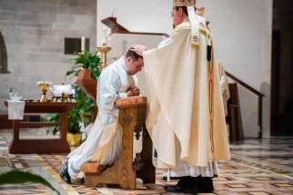 Archbishop Allen H. Vigneron of Detroit lays his hands on Father Matthew Hood to ordain him to the priesthood Aug. 17, 2020, at the Cathedral of the Most Blessed Sacrament. Father Hood, a graduate of Sacred Heart Major Seminary, was originally ordained in 2017.