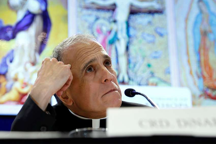 Cardinal Daniel DiNardo, president of the U.S. Conference of Catholic Bishops, looks up while holding a press conference Nov. 12 at the bishops' general assembly in Baltimore.