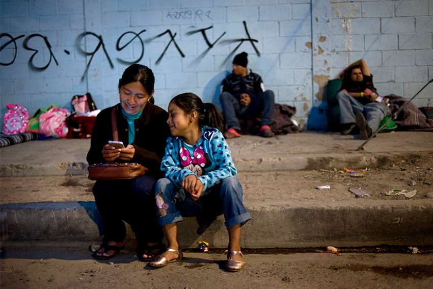 A mother and daughter wait outside a camp at a sports facility in Tijuana, Mexico, set up to for people arriving Nov. 15 in a caravan of Central American migrants at the U.S.-Mexico border. The shelter opened the previous night and had more than 750 people, but dozens more lined up outside waiting to enter.
