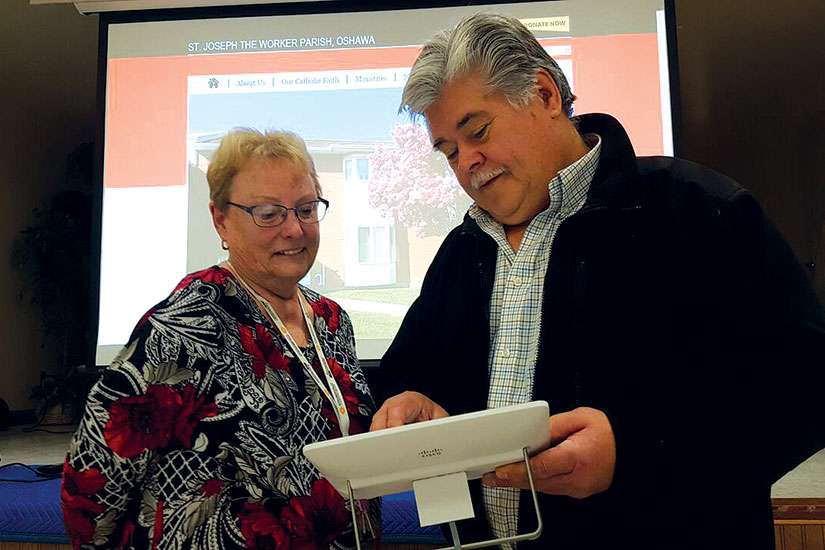 St. Joseph the Worker Oshawa Office Manager Mary Lou Elliot and volunteer Technical Coordinator Bill Kudryk test the recently installed video conferencing equipment funded through the Family of Faith.