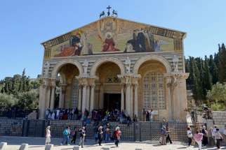 Tourists walk outside the Church of All Nations at the foot of the Mount of Olives in Jerusalem March 28. Pope Francis will meet with priests and seminarians in the church during his pilgrimage to the Holy Land in May.