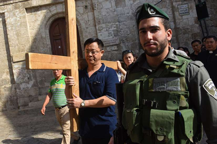 An Israeli border police officer stands near Catholic tourists from Indonesia as they carry a cross Oct. 18 on the Via Dolorosa in Jerusalem's Old City, near a site where several recent stabbings have taken place.