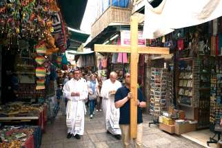 Catholic pilgrims walk past shops selling souvenirs on Via Dolorosa in Jerusalem's Old City.