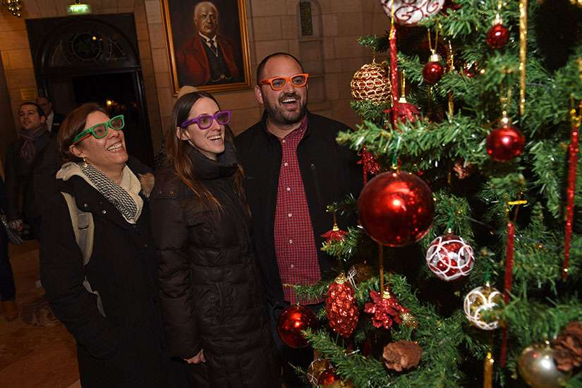 Galit Oren, Tali Khanin, and Zohar Kaplan wear special glasses that make the lights multiply on the Christmas tree in the lobby of the YMCA in West Jerusalem Christmas Eve. They were part of a group of secular rabbinical students who had come to experience Christmas in Jerusalem.