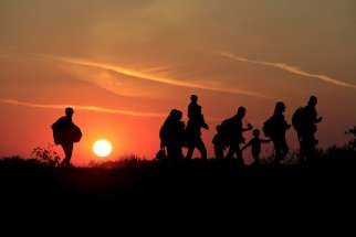 Migrants walk along at sunset after crossing into Hungary from the border with Serbia near Roszke, Hungary, Aug. 29.