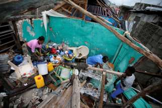 Residents salvage items from their destroyed home Oct. 5 after Hurricane Matthew swept through Les Cayes, Haiti.