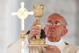 Pope Francis elevates the chalice during Mass outside the Basilica of St. John Lateran in observance of the feast of Corpus Christi in Rome June 2015.