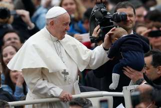 Pope Francis greets a baby during his general audience in St. Peter's Square at the Vatican April 11.