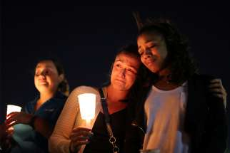 Masses and prayer services have been taking place across the city since the shooting. Women weep during a candlelight vigil Oct. 3 in memory of the victims of a mass shooting along the Las Vegas Strip.