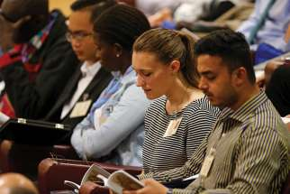 Emilie Callan, a synod delegate from Canada, second from right, attends a session of the Synod of Bishops on young people, the faith and vocational discernment at the Vatican Oct. 11.