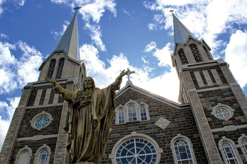 A Christ statue stands outside Sts. Paul and Peter Church in Baie-Saint-Paul, in the Archdiocese of Quebec, which is  re-organizing its parishes.